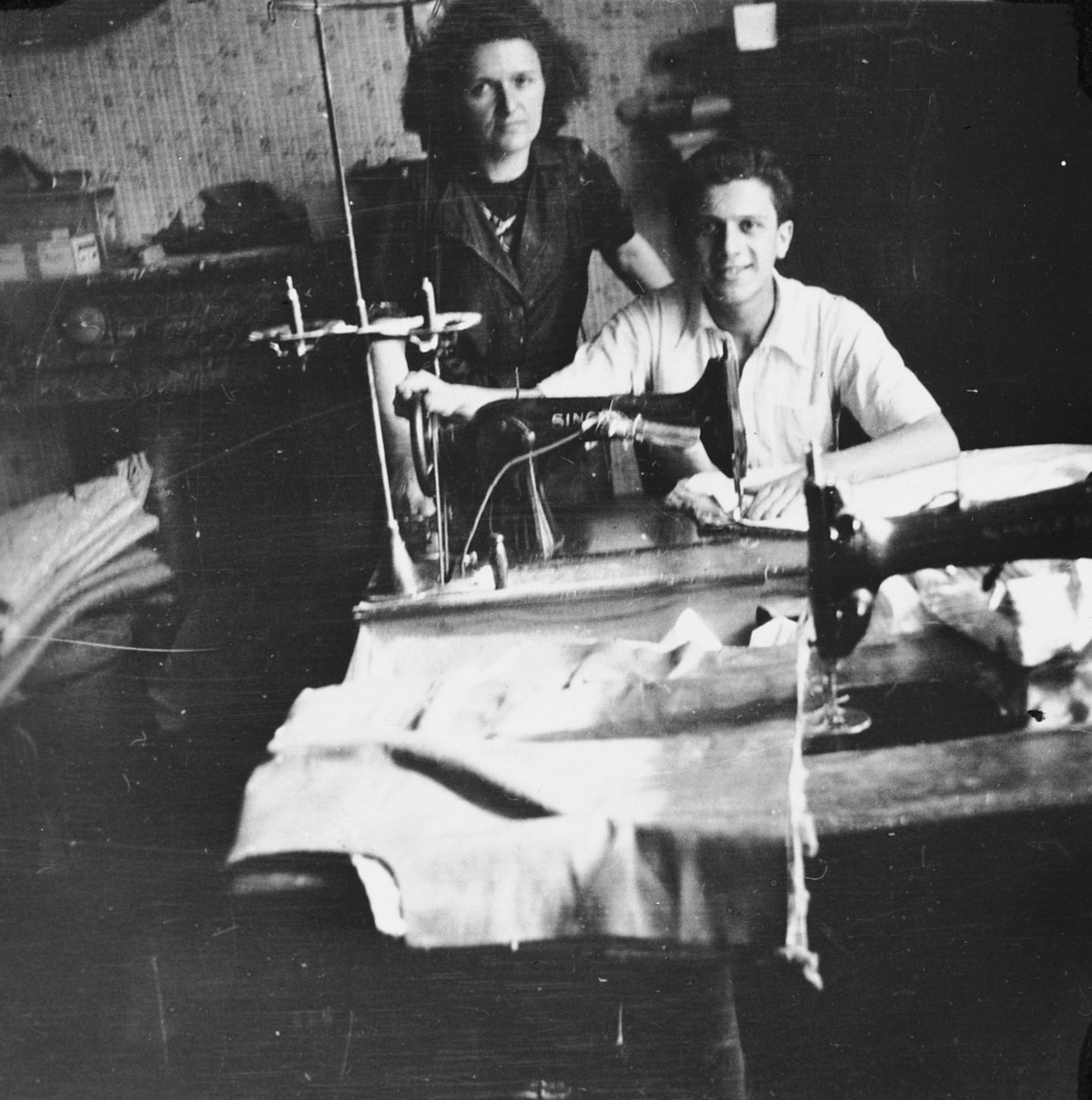 A Jewish woman who is living in hiding as a Christian in a factory in Brussels, poses with a young man who is seated at a sewing machine.  Pictured is Fani Mendelowicz.