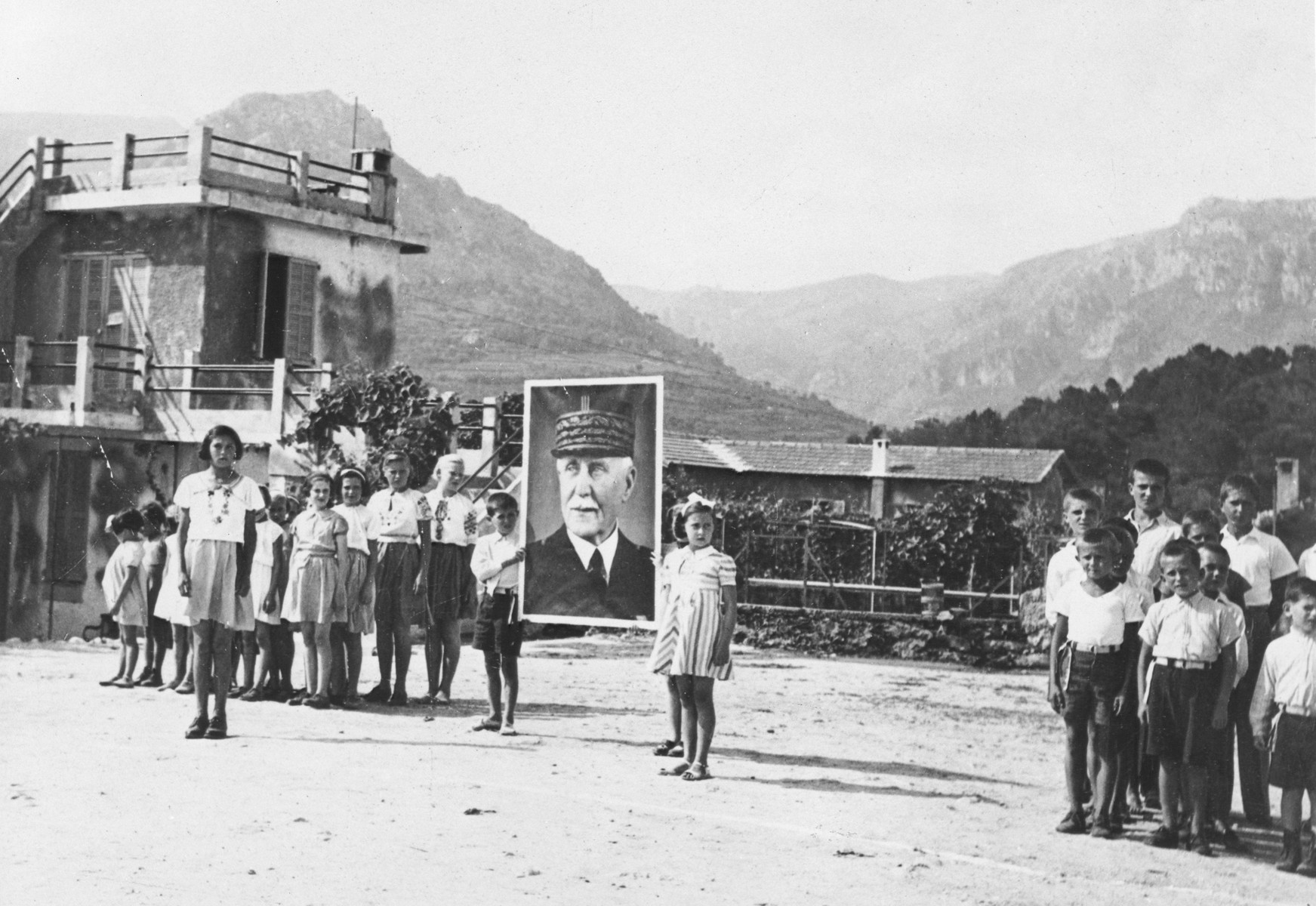 Jewish and Czech refugee children stand at attention holding a large portrait of Petain in the courtyard of the MACE children's home in Vence.