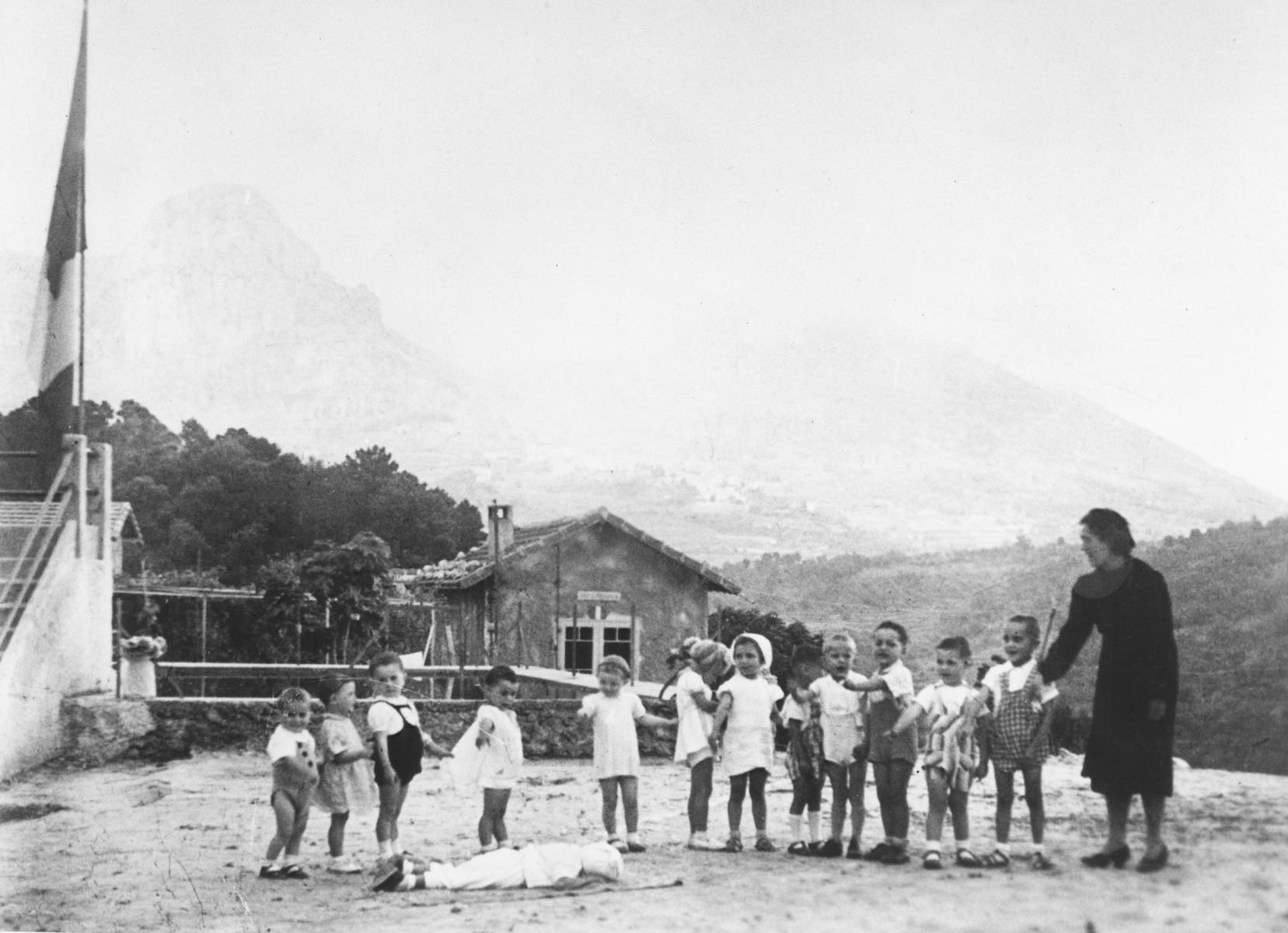 Miss Hermanova, a Czech Jewish nursery teacher, leads a circle game in the MACE children's home in Vence.
