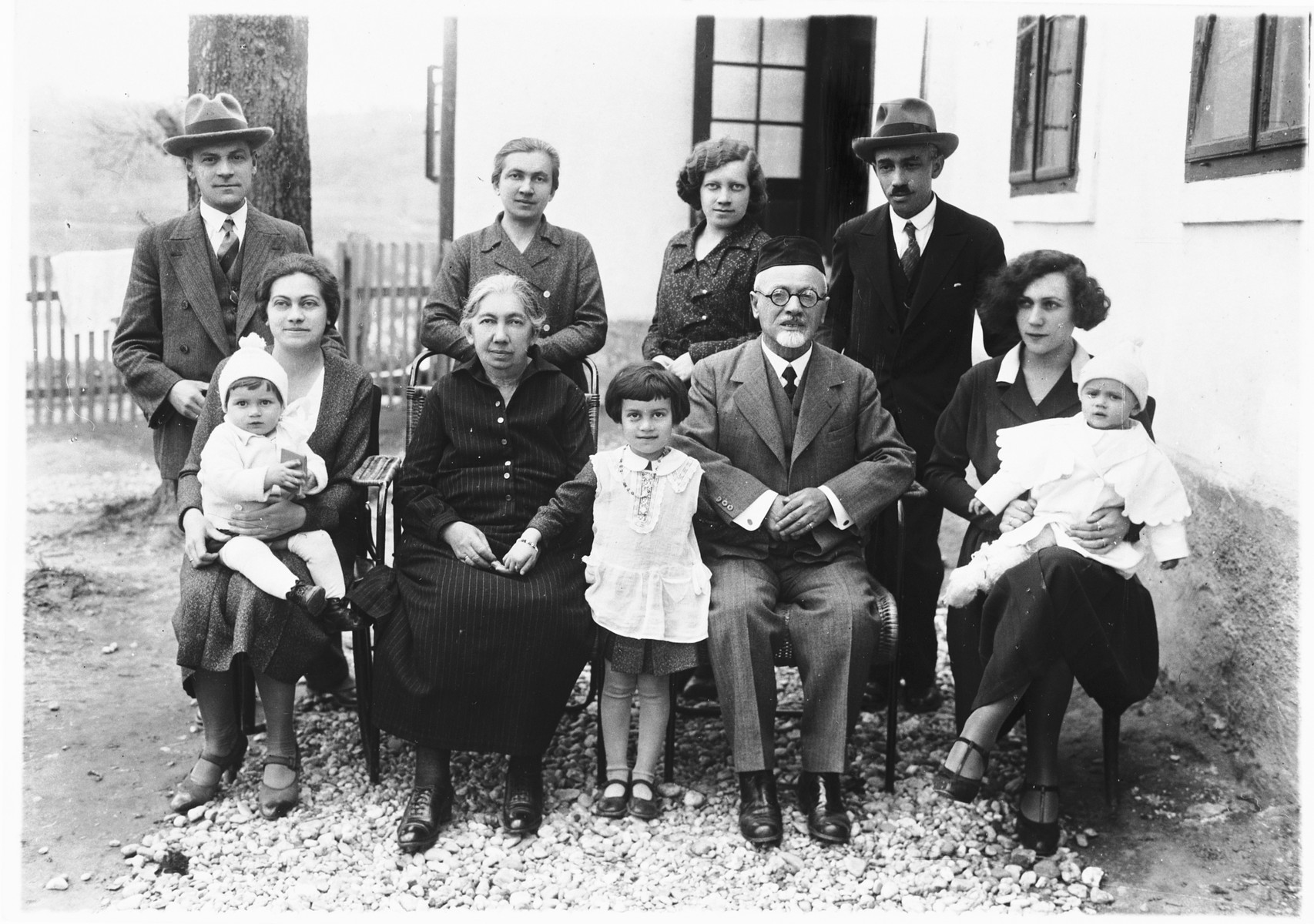 Members of the Deutsch family pose outside their home in Ludbreg, Croatia, which also functioned as the local synagogue.  Pictured sitting from left to right are: Blanka (Deutsch) Apler with her daughter Vera, Katarina Deutsch, Zdenka Apler, Rabbi Leopold Deutsch and Ida Deutsch with her daughter Edita.  Standing from left to right are: Rudi Apler, Giza Deutsch, Silva Deutsch and Erne Deutsch.