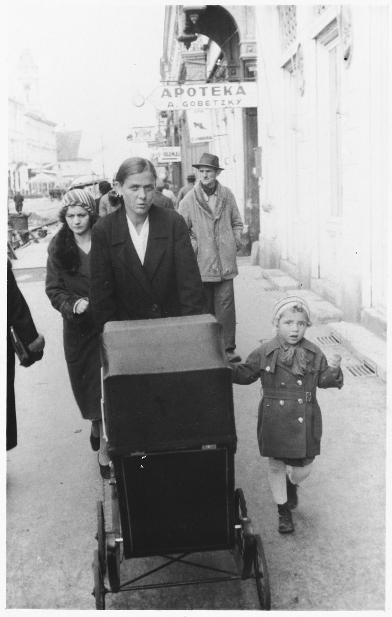 A young Jewish child walks along a street with her nanny and baby sister (in a carriage) in Osijek, Croatia.  Pictured is Miriam Spitzer (right).