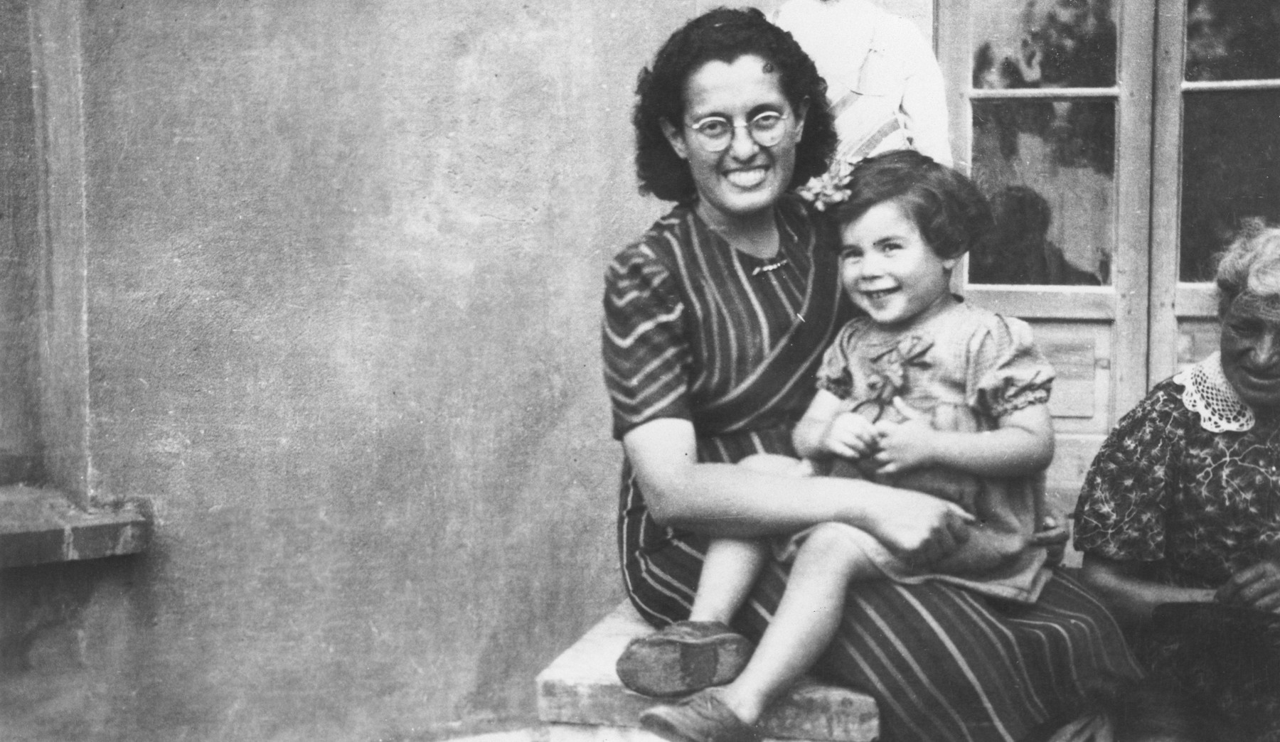 Mlle. Hermanova, a Czech Jewish nursery teacher, holds a young toddler on her lap.  The toddler pictured is Ryfka Isacovic, from  Czechoslovakia., who stayed in Joseph Fisera's MACE school in Vence during the war.