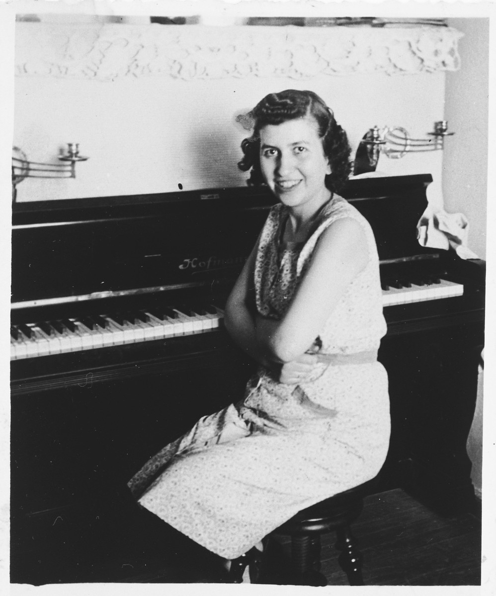 A young Jewish woman poses next to the piano in her home.  Pictured is Aime Levy.