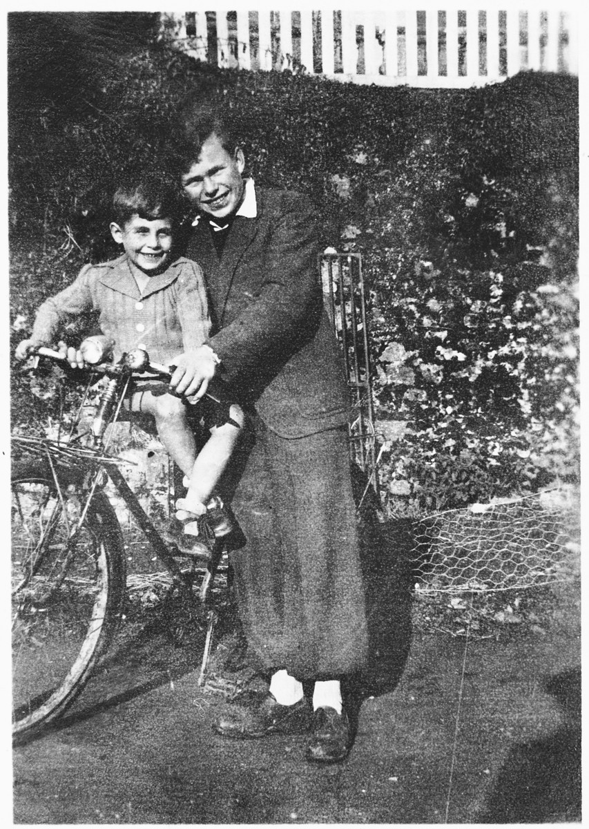 Herbert Karliner, a German Jewish refugee youth helps a younger refugee child, Charles Mandell, ride a bicycle in the Masgelier children's home.