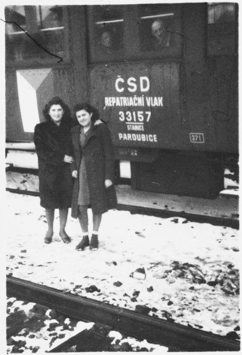 Two teenage Jewish DPs who have joined a children's transport pose outside the train that will take them from Prague to Paris.
