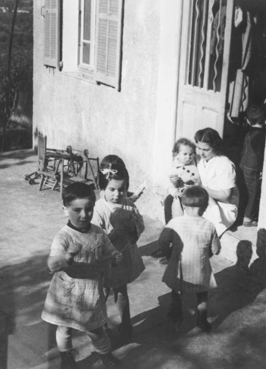 Todlers gather around a female care-giver in the MACE children's home in Vence.