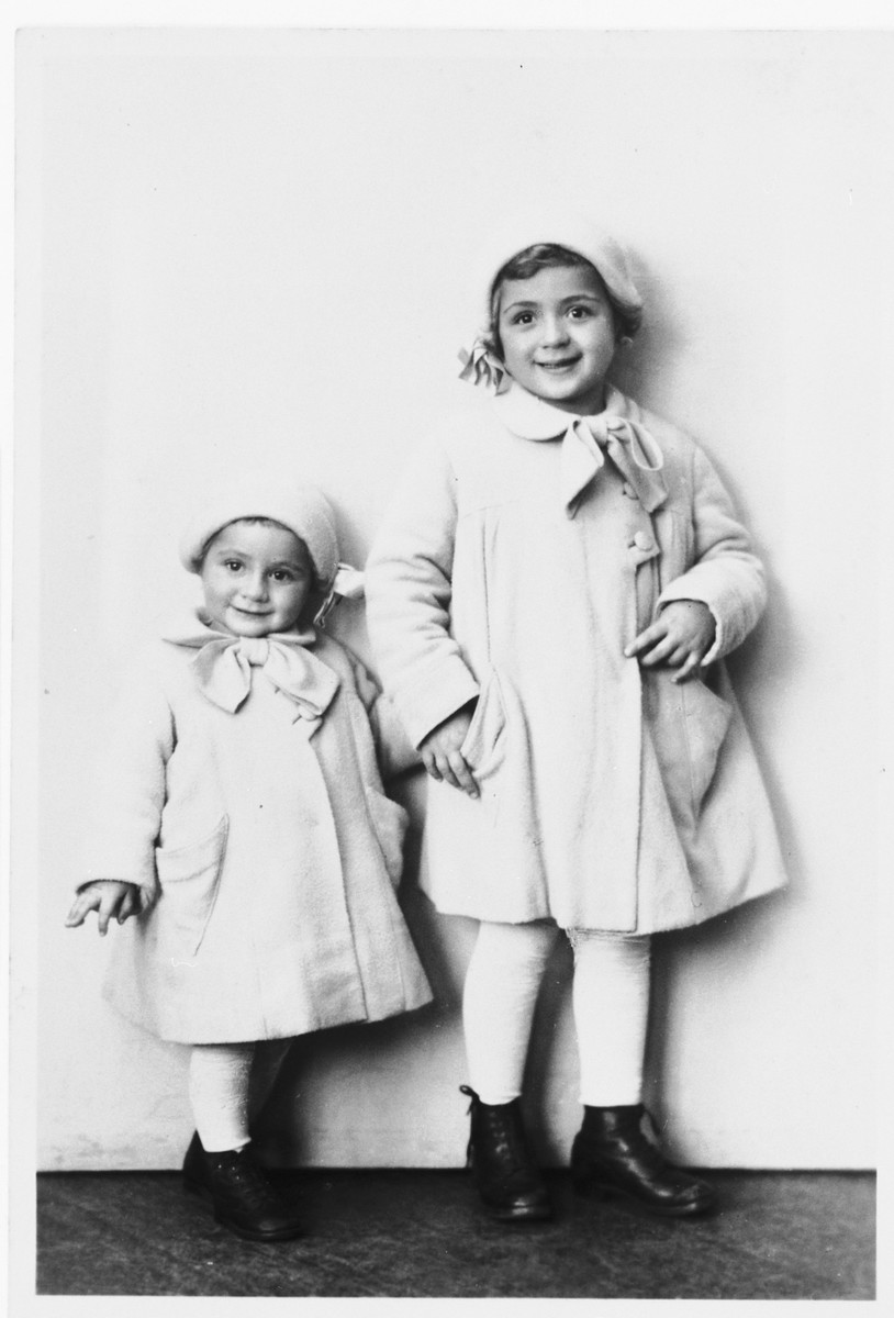 Studio portrait of two Jewish sisters dressed in matching coats and hats.   Pictured are Miriam and Leah Spitzer.