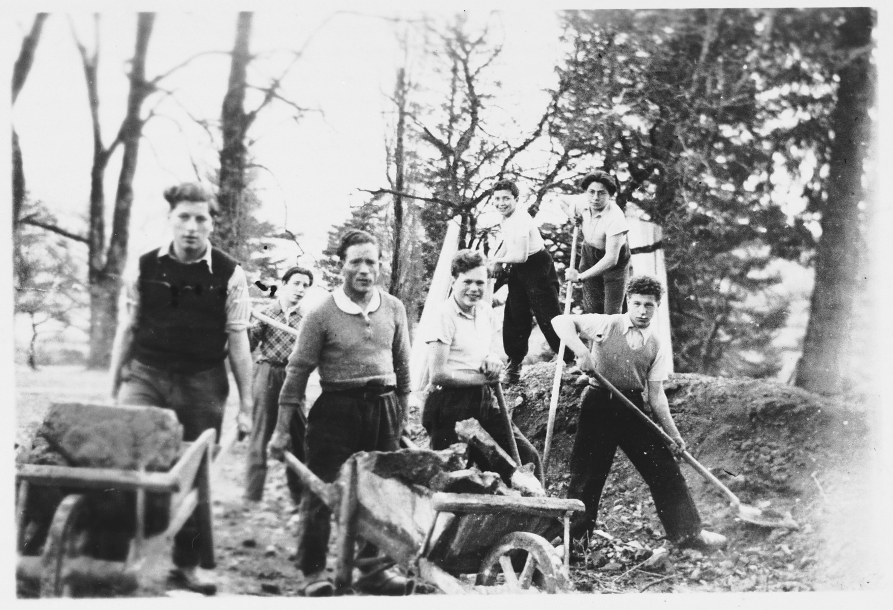 A group of Jewish refugee youth work outside with hoes, rakes and wheelbarrows at the Masgelier children's home.