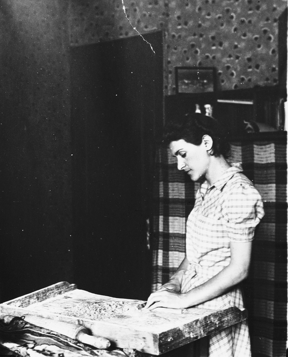 A young Jewish woman prepares homemade noodles in the kitchen of her apartment in Antwerp.  Pictured is Leah Ciechanow.