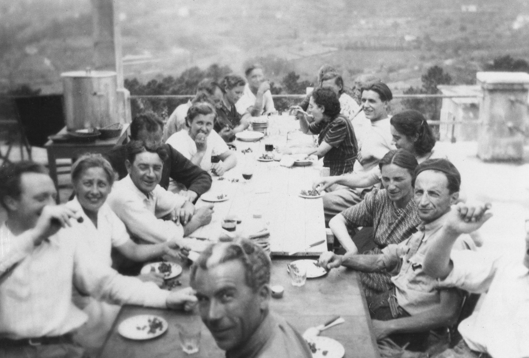 The staff of the MACE (Maison d'Accueil Chretienne pour Enfants) children's home at Vence eats a meal outside on the home's terrace.  Joseph Fisera is pictured in the front facing the camera.