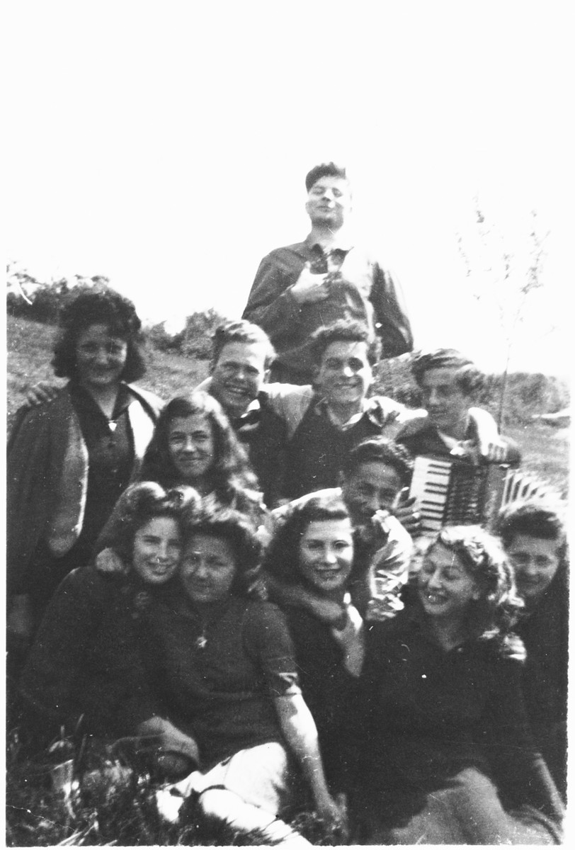 Group portrait of Jewish DP youth outside the Poulouzat children's home. One of the teenagers plays an accordion.  Among those pictured are Manfred Rosenberg (standing at the back) and Herbert Karliner (third row, third from the right.