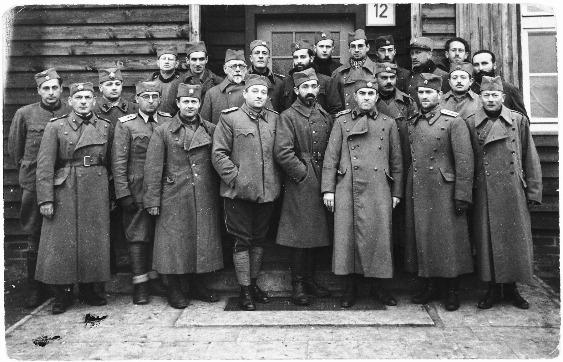 Group portrait of Yugoslavian soldiers in a POW camp in Osnabrueck, Germany.  Among those pictured is Marko Spitzer (front row, fifth from right), Yugoslavian writer, Stanislav Vinaver (fourth from the left) and Ljubomir Popovic (front row, last on right).