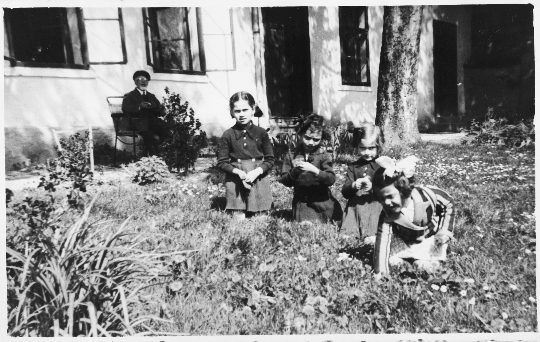 Four young Jewish girls play in the garden while their grandfather looks on.  Pictured are Zdenka and Vera Apler and Edita Deutsch.  In the background is Rabbi Leopold Deutsch.  He is seated in front of a building that served both as the Deutsch home and the local synagogue.