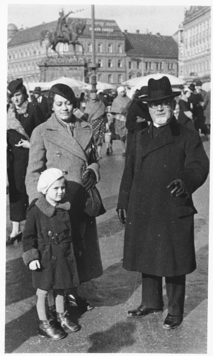A young Jewish girl poses on a street in Zagreb with her mother and grandfather.  Pictured are Vera Apler (the child in the foreground) with her mother, Blanka (Deutsch) Apler and grandfather, Rabbi Leopold Deutsch.