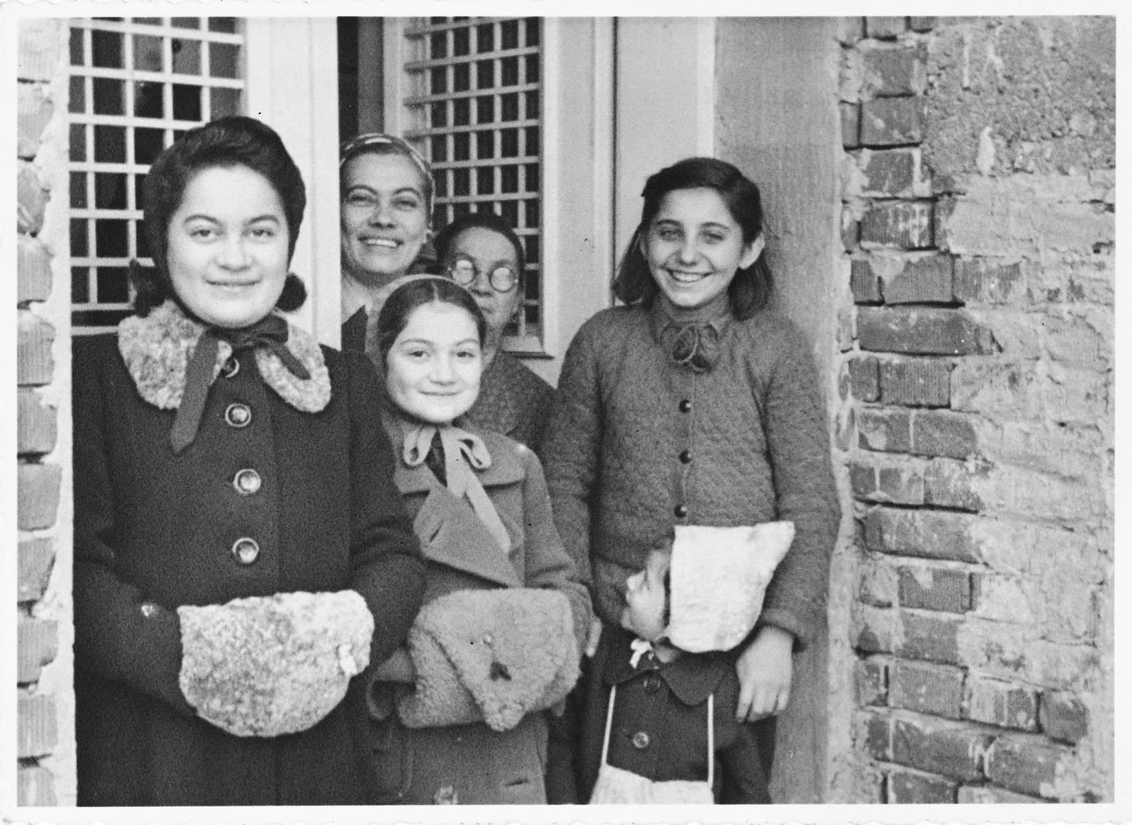 A Jewish family poses with their Croatian neighbors and friends.  Pictured in the ffront from left to right are: Zdenka and Vera Apler and their young cousin Dorica (Theodora) Basch.  Standing behind them are Blanka Apler (the mother of Vera and Zdenka), Maria Runjak and Stefica Grabaric.