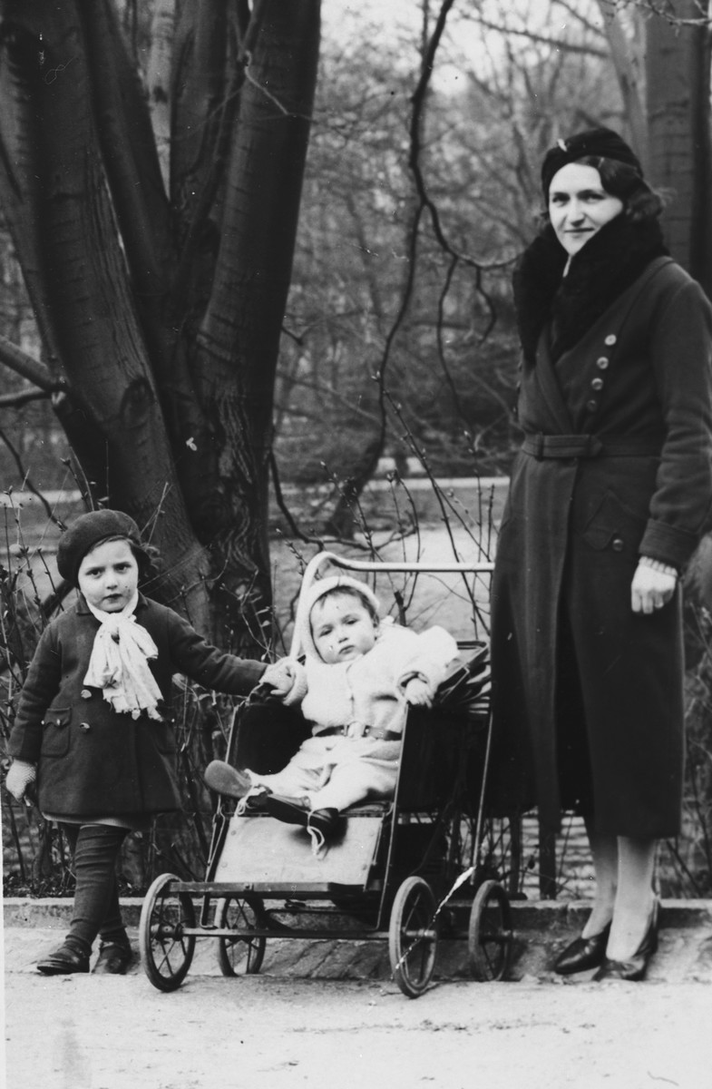 A Jewish mother poses with her two young children in a park in Antwerp, Belgium.  Pictured from right to left are: Fani, Charlotte and Flora Mendelowicz.