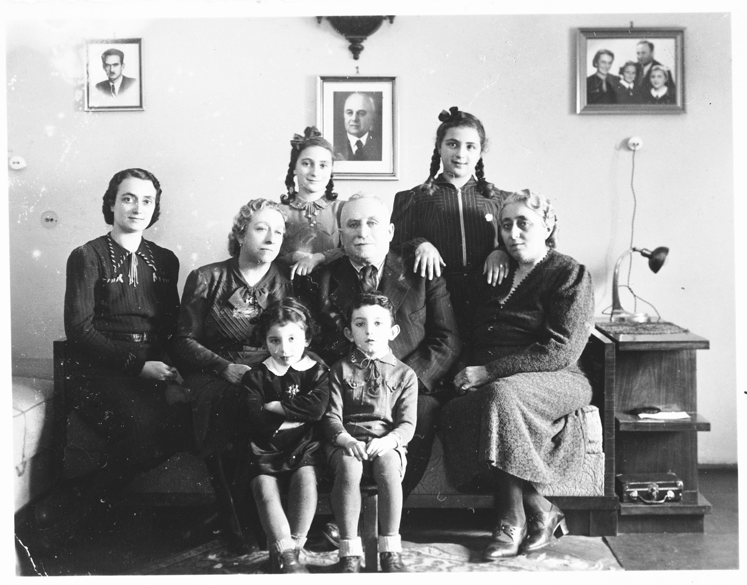 A Jewish family poses in their apartment with two young Jewish children they are taking care of, who were recently released from the Djakovo concentration camp.  Pictured are members of the Spitzer family shortly before the deportation of the Jewish community of Osijek. Standing in the back row, form left to right are Leah and Miriam Spitzer; in the middle row are Ilonka Spitzer, Riza Krasso and Mr. and Mrs. Spitzer, the parents of Marko Spitzer.  At the time of this photograph, Marko Spitzer was already in a POW camp, and Alfred Krasso was imprisoned in Jasenovac.