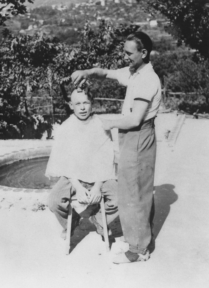 Edward Mikula, a Czech miner from Belgium, shaves the head of Thomas Krochmal, a Jewish child on a farm near Vallon where they are hiding under the protection of MACE.