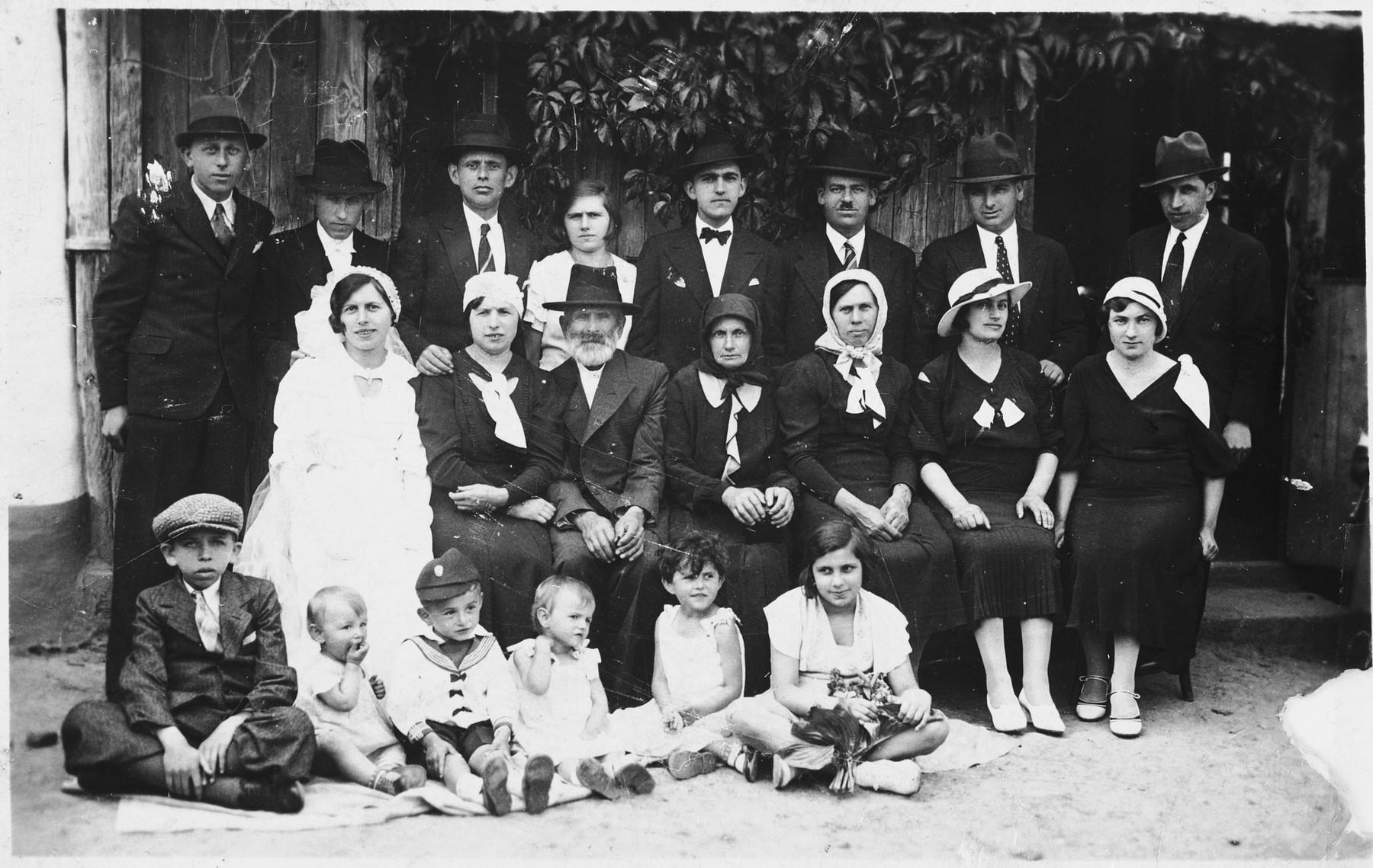 Relatives of the bride and groom pose for a family portrait at a Jewish wedding in Bilki.  Pictured in the front row from left to right: Zoltan Berger, Violet Mermelstein, Israel Mermelstein, Hana Mermelstein, Magda Mermelstein, and Eva Zocher.  Middle row:  Rezsi (Weisz) Berger (bride), Bela (Weisz) Mermelstein, Avruham Weisz, Henja Rochel Weisz, Sura Berger, Rozsi Zocher, Raizel (?).  Top row: Sanye,  Aaron Berger (groom), Ludwig Mermelstein, Choli Weisz, Samu Berger, Samu Zocher and Lajos Weisz.