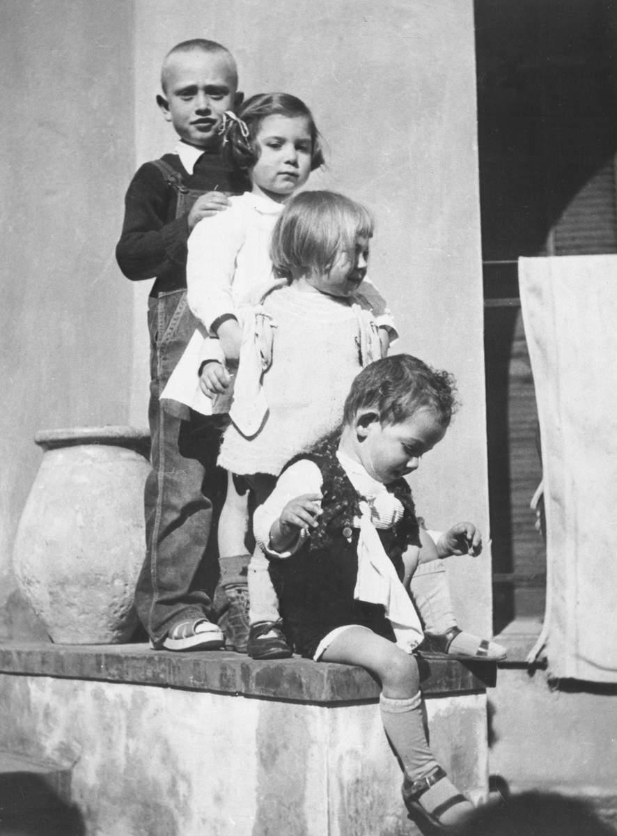 Four Jewish children stand in a row on the steps of the children's home in Vence.  In the back is Farkas and in front are three Mermelstein children.