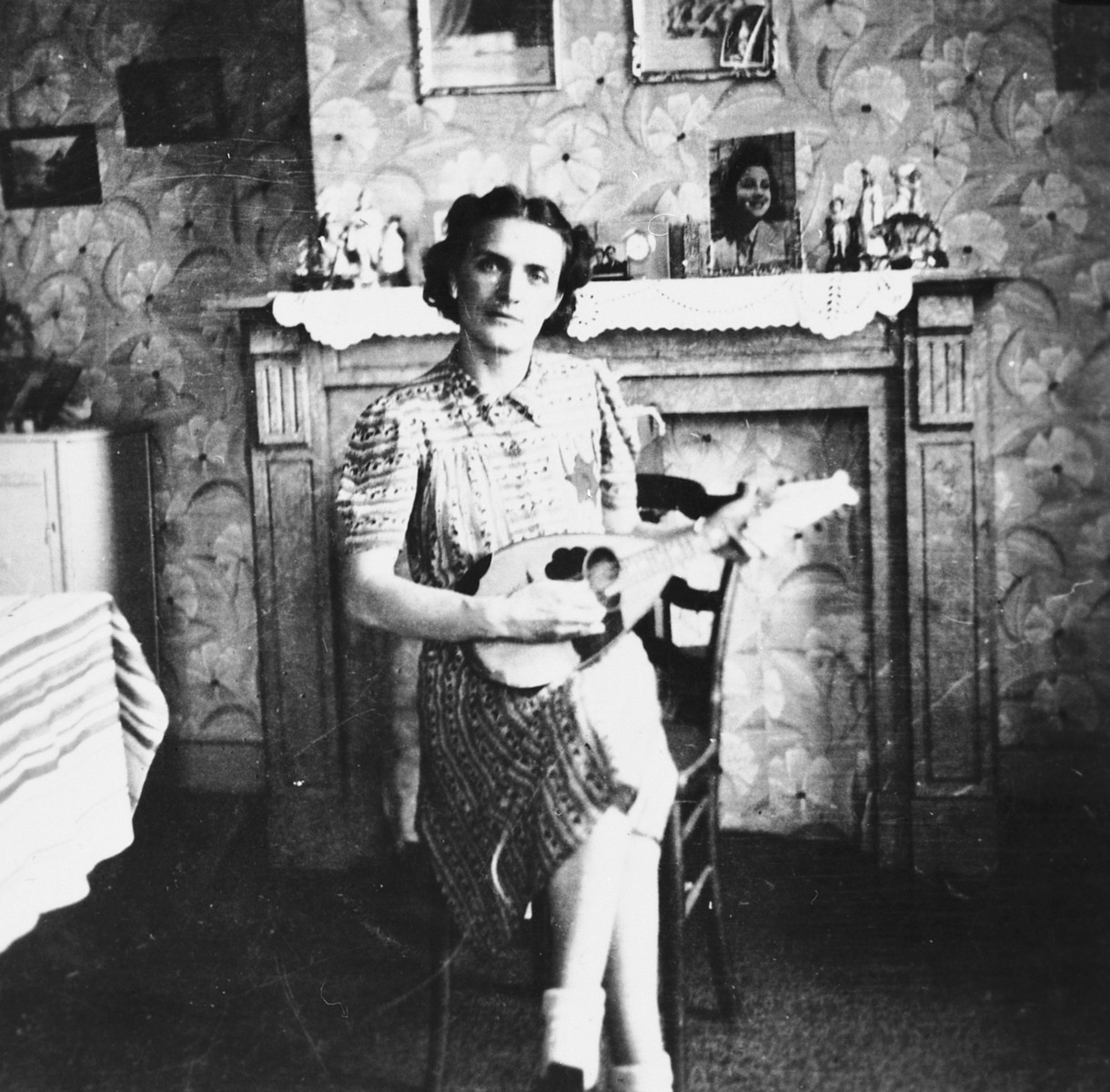 A Jewish woman living in hiding as a Christian, plays the mandolin in her apartment in Brussels.  Pictured is Leah Ciechanow.  She was subsequently deported to her death in Auschwitz.