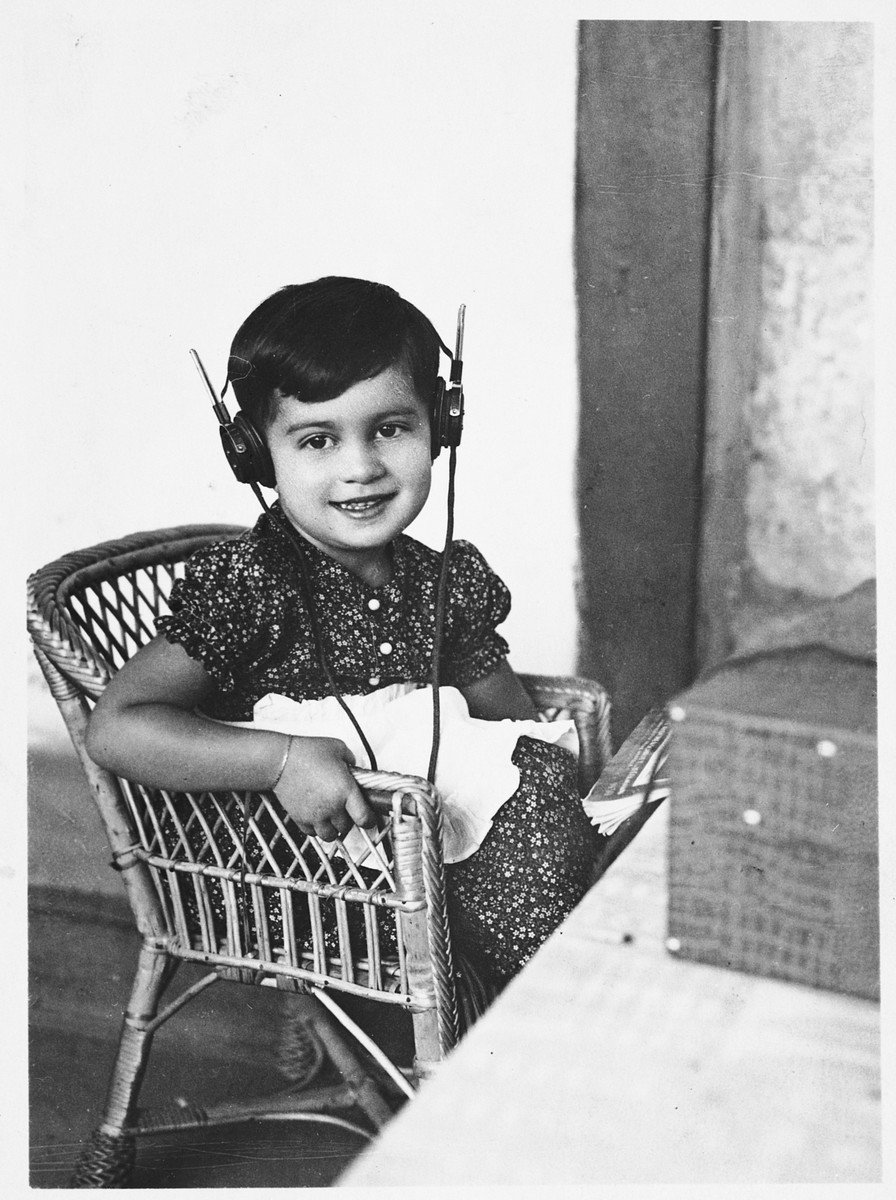 A young Jewish girl listens to a radio with head phones.  Pictured is Zdenka Apler.