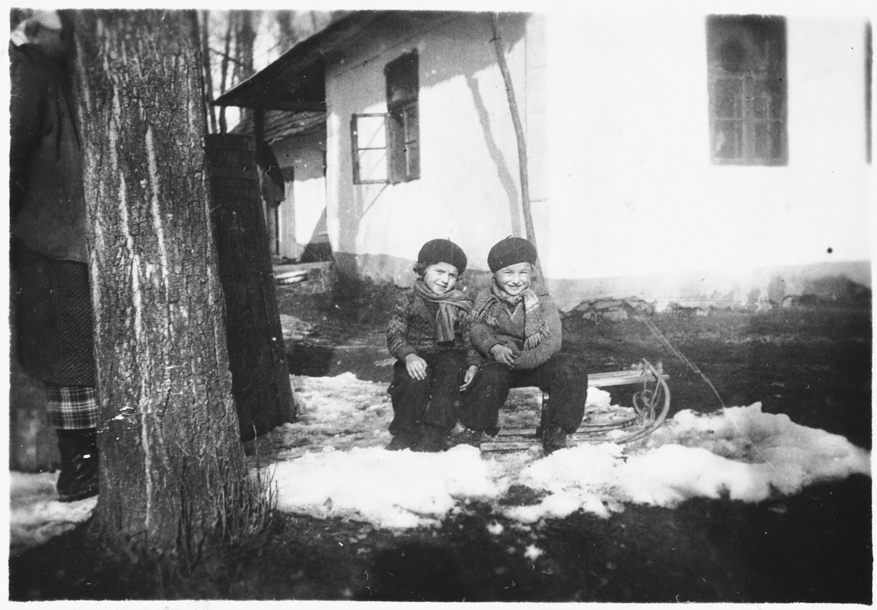 Two young Jewish children sit outside in the snow in front of their house in Bilki.  Pictured are Violet and Hana Mermelstein.
