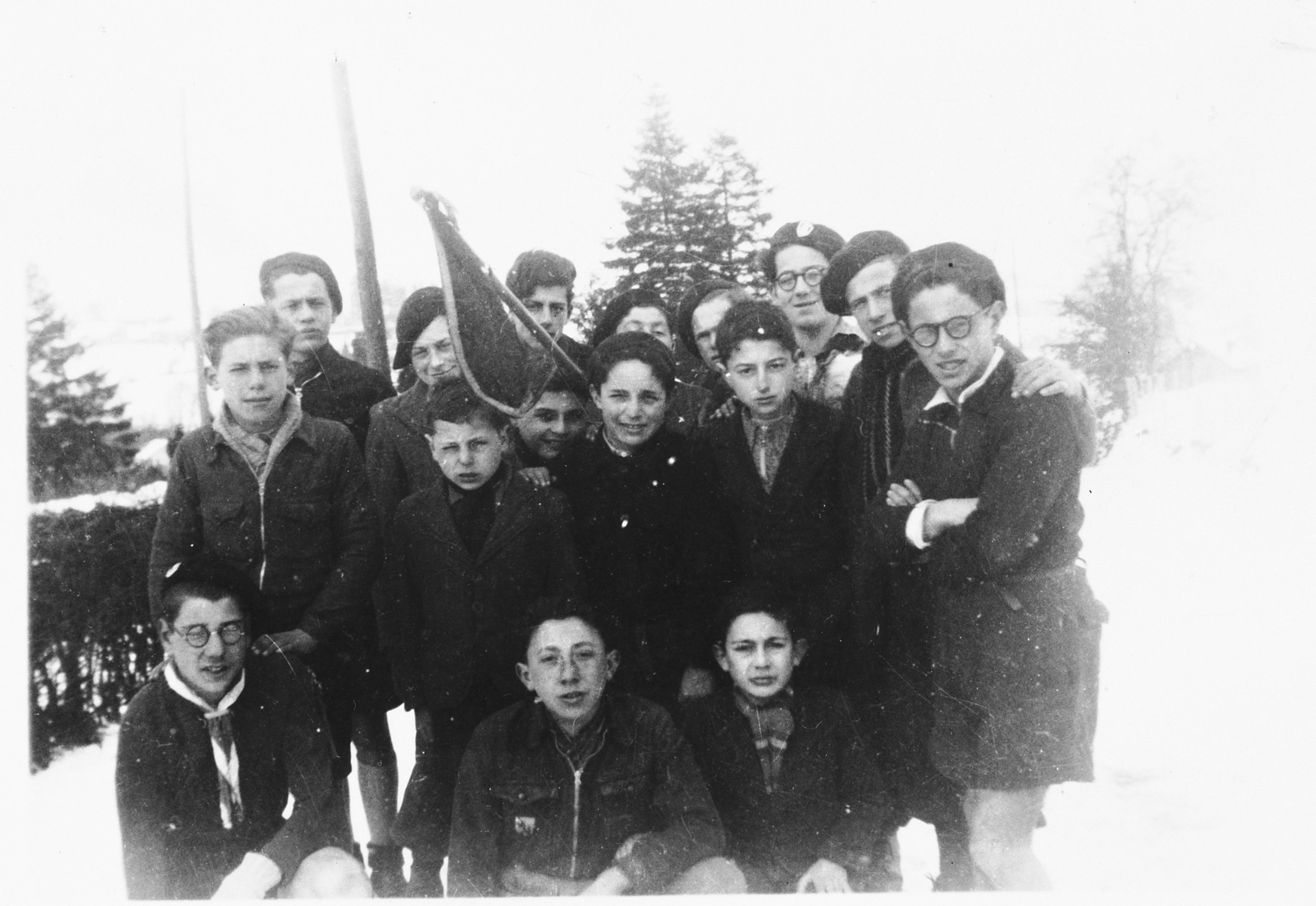 Group portrait of Jewish DP youth from the Poulouzat children's home outside in the snow.   Among those pictured are Herbert Karliner (back row, fifth from the right, partially obscured) and Charles Valmy (standing at the right).