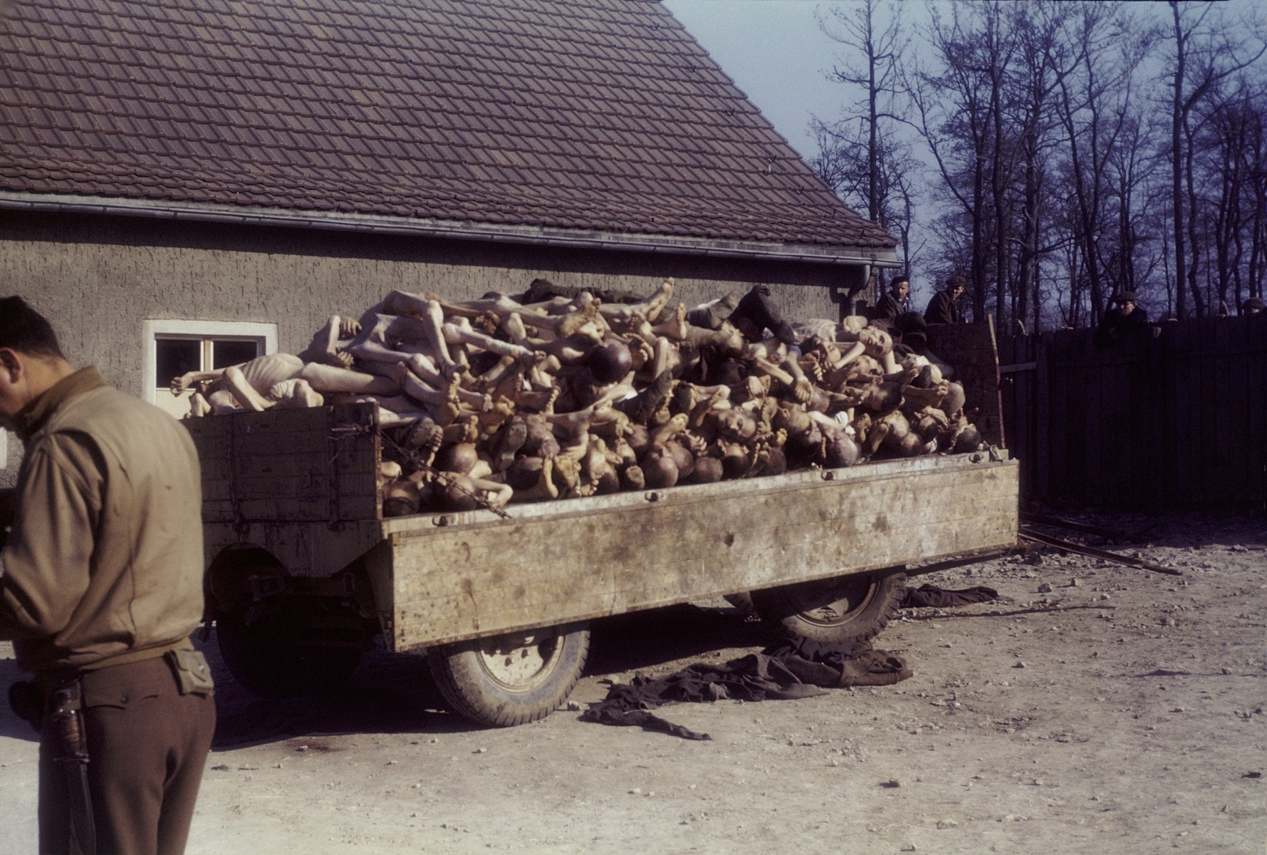 An American soldier stands near a wagon piled high with corpses outside the crematorium in the newly liberated Buchenwald concentration camp.