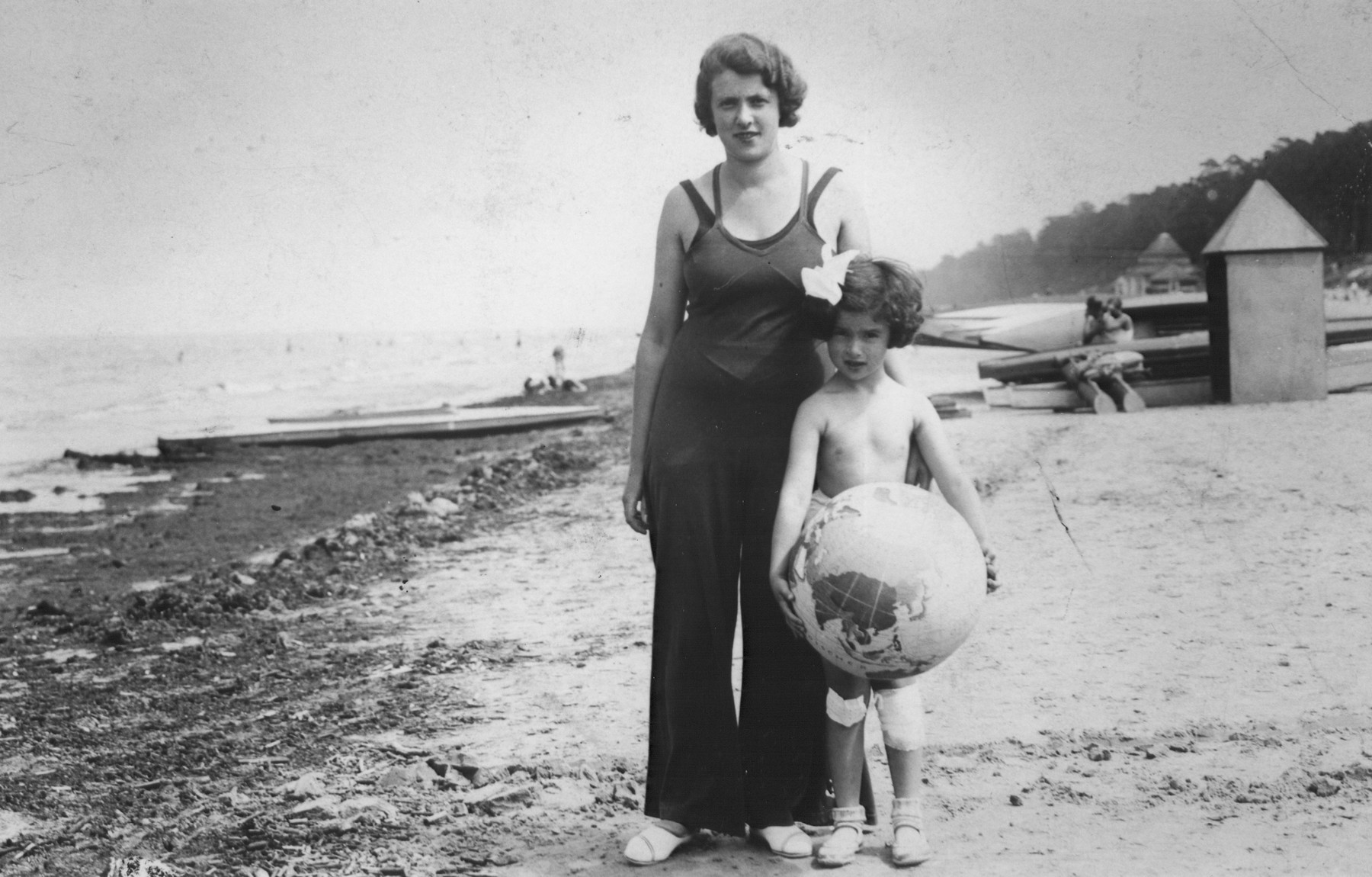 A young Jewish child holding a beach ball painted like a globe, poses with her mother on a beach near Vilna.   Pictured are Mira Jedwabnik and her mother, Lydia.