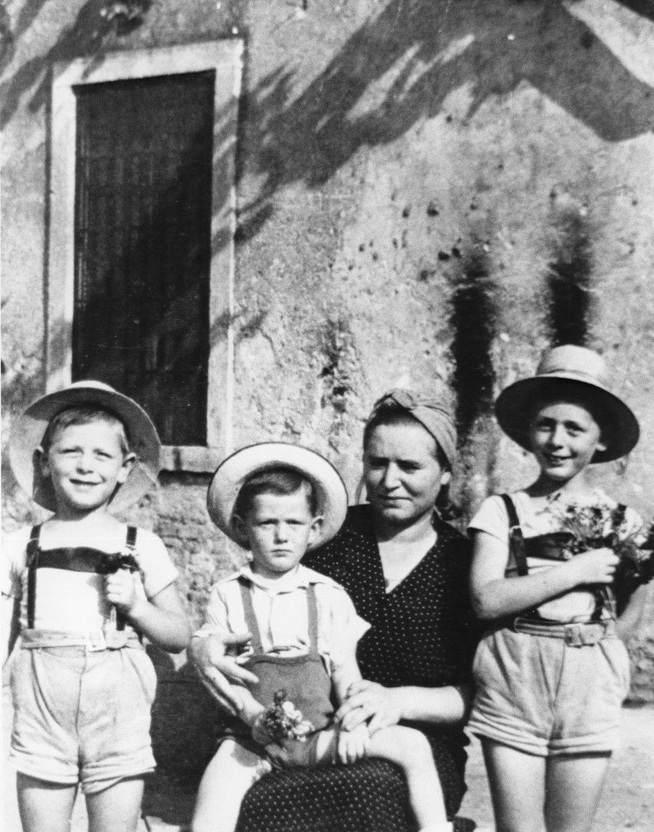A Jewish refugee family from Croatia sits outside their lodgings in Malo, Italy, where they have been confined by the Italian authorities.  Pictured are Gabriela Deutsch sits and her three sons, Pavel, Branko and Djordje.