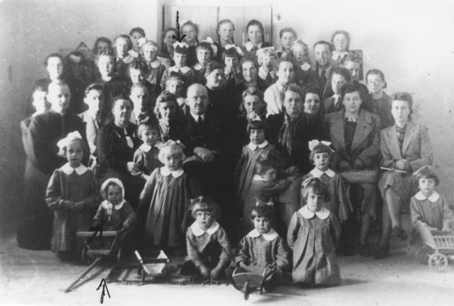 Group portrait of pupils and teachers in the Christian Sisters of Klimontow convent school in Klimontow, Poland.  Among those pictured is the hidden Jewish child, Mania Sztajnman (front row, left, at the arrow).  Also pictured is a Polish pupil, Krysia Cichos (second row from the top, center with a bow in her hair), who sent this photo to Mania in 2002, and Sister Maria Herman, the principal of the school (directly above Mania).