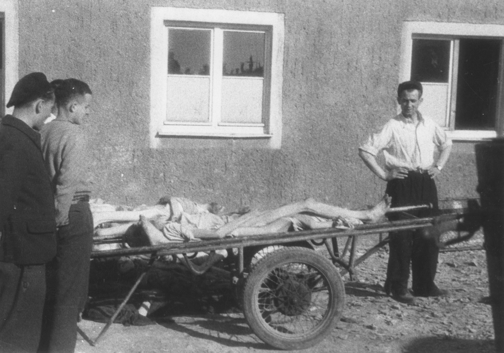Survivors stand next to a cart loaded with corpses outside the crematoria in the newly liberated Buchenwald concentration camp.
