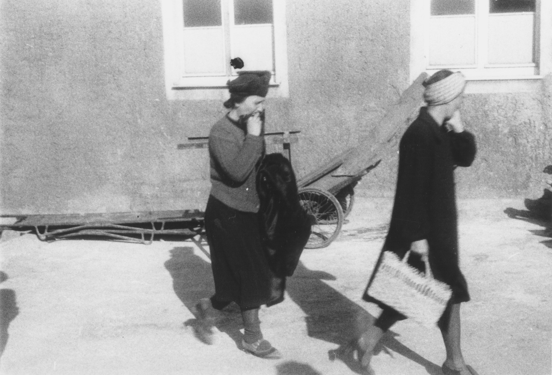Two German women file past piles of corpses outside the crematorium in the newly liberated Buchenwald concentration camp.
