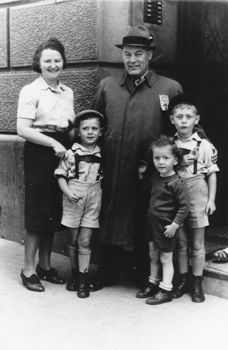 Members of the Deutsch family pose outside their home in Zagreb with an Austrian Jewish refugee who was living with them, Zagreb, 1941.  Pictured is Josef Deutsch (wearing a Jewish badge) with his three children, Pavel, Branko and Djordje, and his boarder, Anni Schiff.