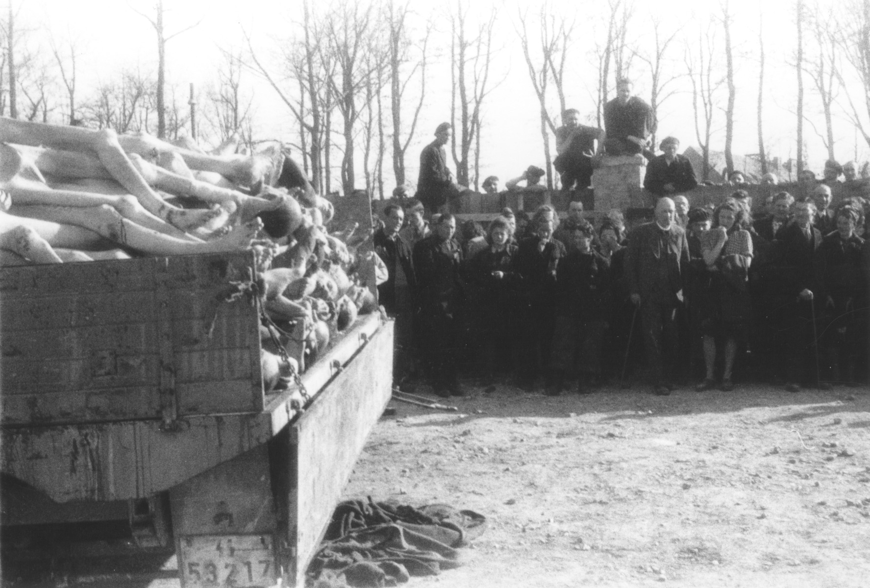 German civilians view a wagon piled high with corpses in the newly liberated Buchenwald concentration camp.