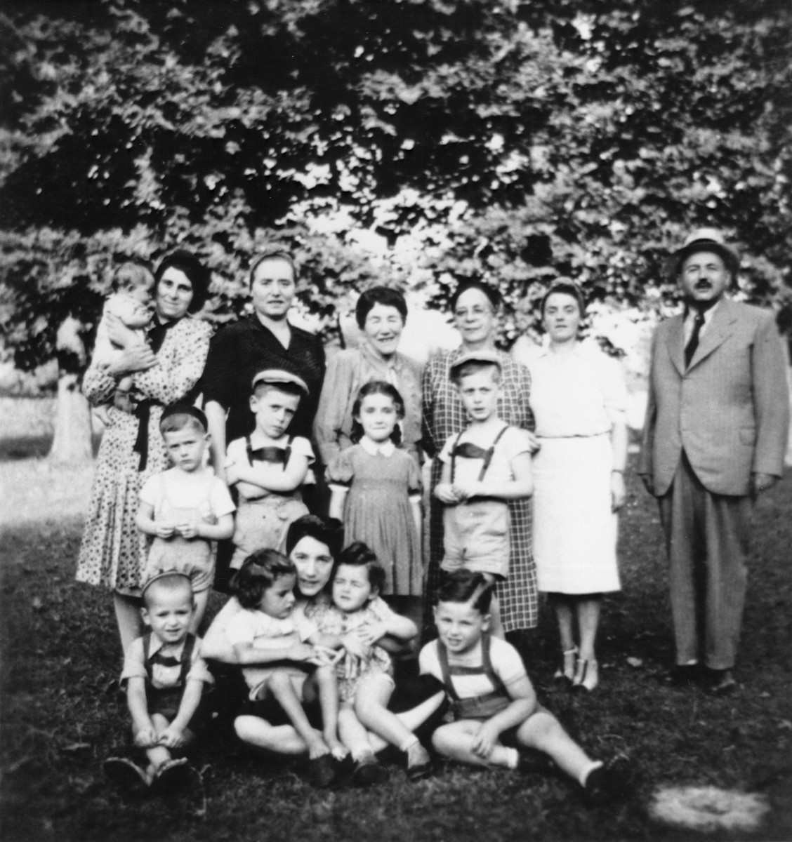 Group portrait of members of three Jewish refugee families in Malo, Italy, where they have been confined by the Italian authorities.  Pictured in the front row (left to right) are: Danko Buchler, an unidentified woman holding Miriam Rothhstein and an unidentified child, and Ari Rothstein. In the middle row from left to right are: Djordje Deutsch, Branko Deutsch, the Buchler daughter, and Pavel Deutsch.  In the back row from left to right are: Renee Buchler holding her baby daughter, Gabriela Deutsch, unknown, Mrs.  Milica Buchler, Mrs. and Mr. Rothstein.
