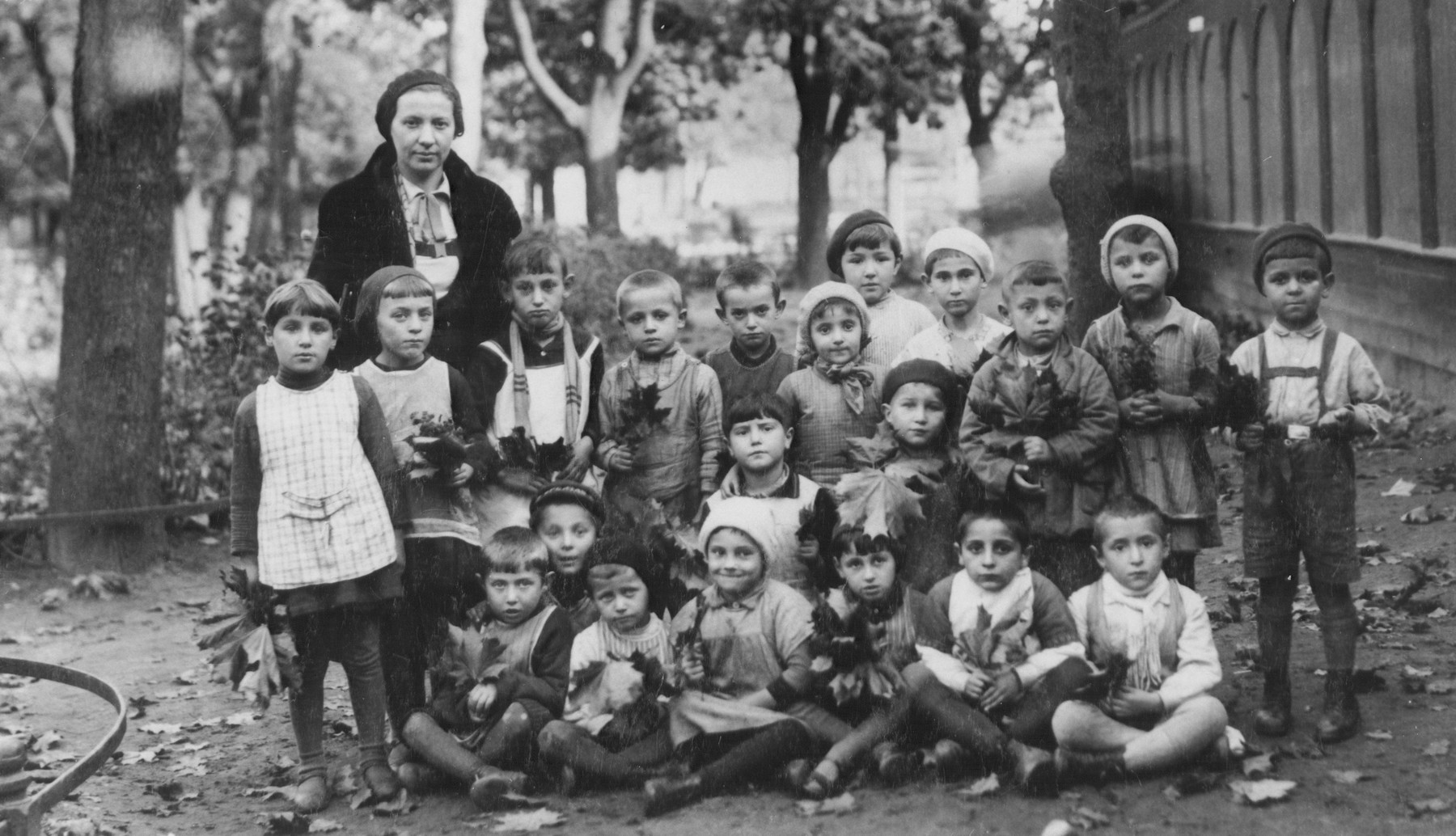 Children from the Jewish kindergarten (located at 9 Mapu Street) in Kovno, Lithuania, pose outside holding leaves.