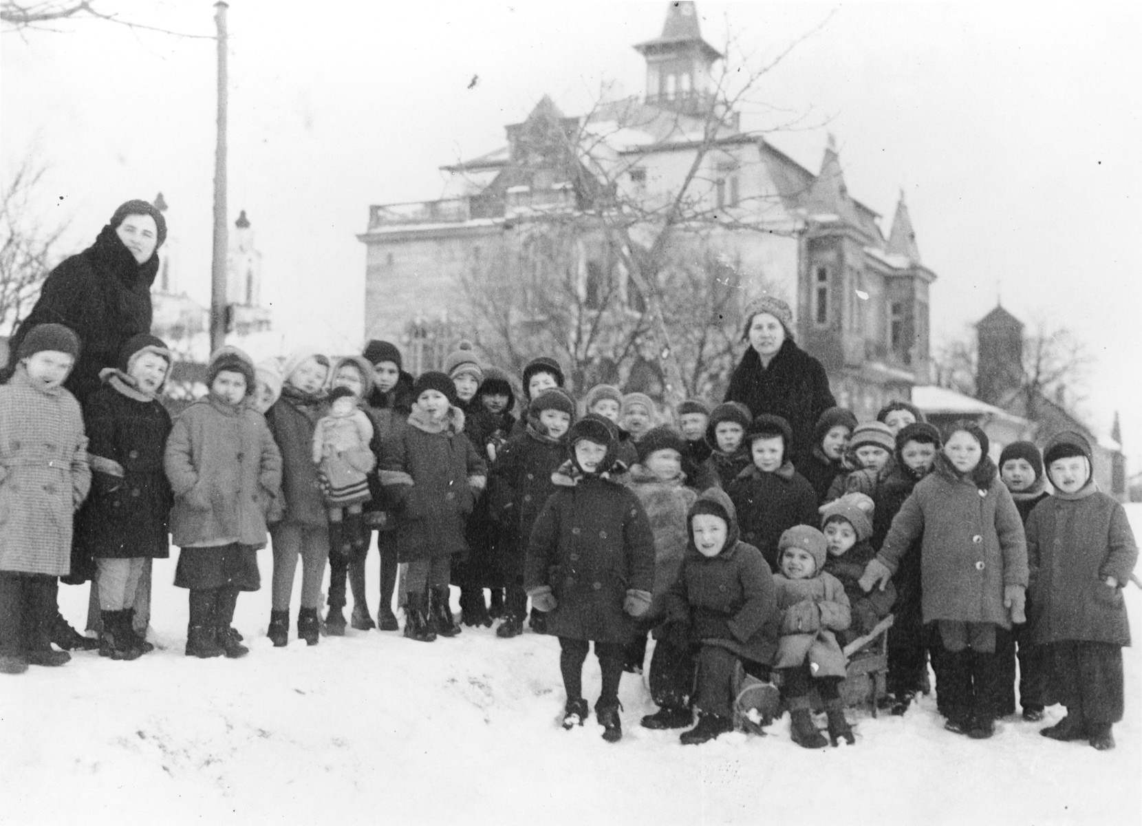 Children from the Jewish kindergarten (located at 9 Mapu Street) in Kovno, Lithuania, pose outside in the snow.