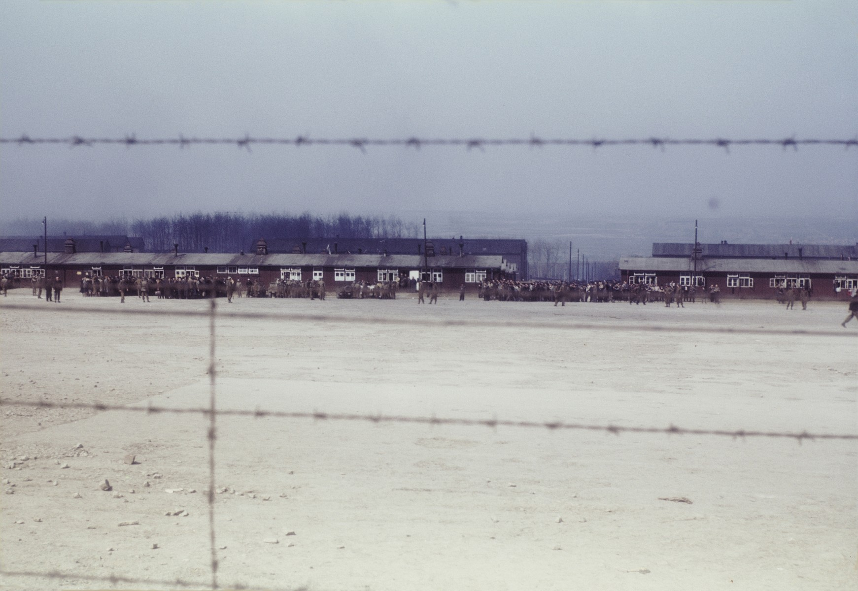 View through the barbed wire fence of survivors gathered outside a row of barracks in the newly liberated Buchenwald concentration camp.