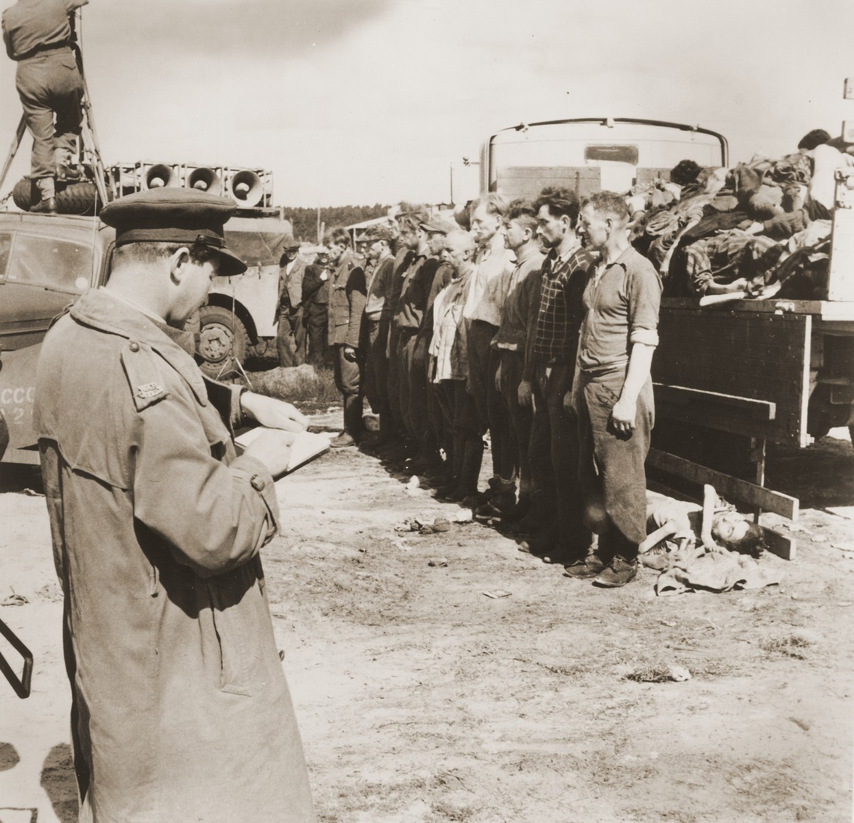 Former camp personnel, including Dr. Fritz Klein, once the camp doctor of Auschwitz and Bergen-Belsen, [third from the right] wait for orders to bury the corpses heaped on the truck behind them.