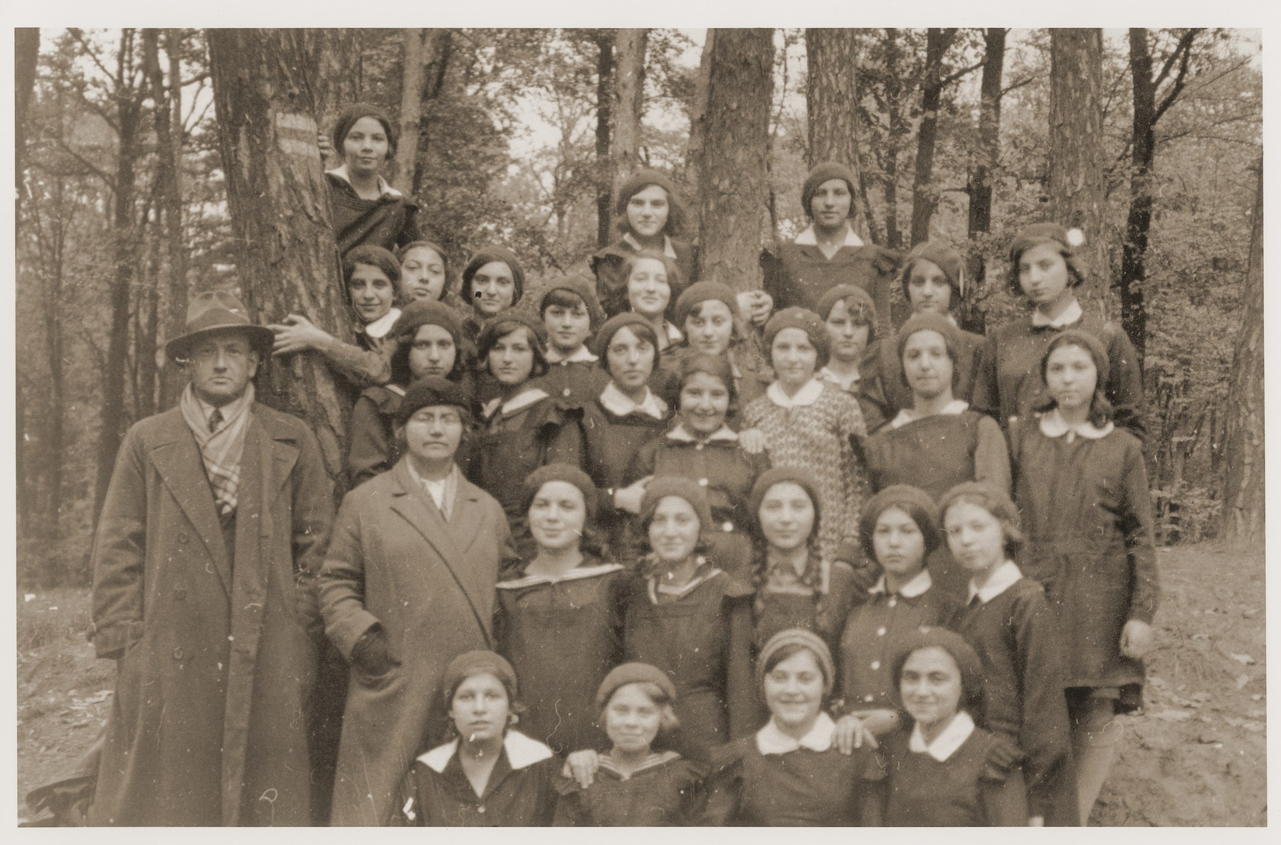 Group portrait of students and teachers of the Yehudia Jewish gymnasium for girls during an outing to a forest.