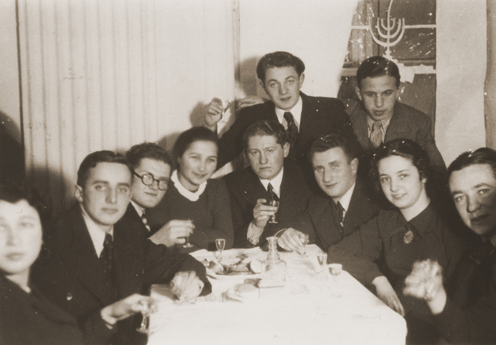 A group of Jewish friends gather in a private home for a farewell party for Rivka Radzinski prior to her departure for Palestine.  Rivka is pictured second from the right.  The photograph is inscribed to Rivka by her friend, Itzhak.
