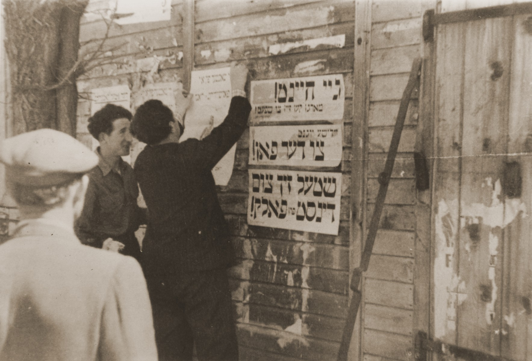 "DPs post signs on the outside of a building at the Neu Freiman displaced persons camp urging Jewish youth to go to Palestine.  The Yiddish signs read, ""Go today-- Tomorrow will be too late!""; ""Jewish youth, to the flag""; and ""Put yourself at the service of the people!"""