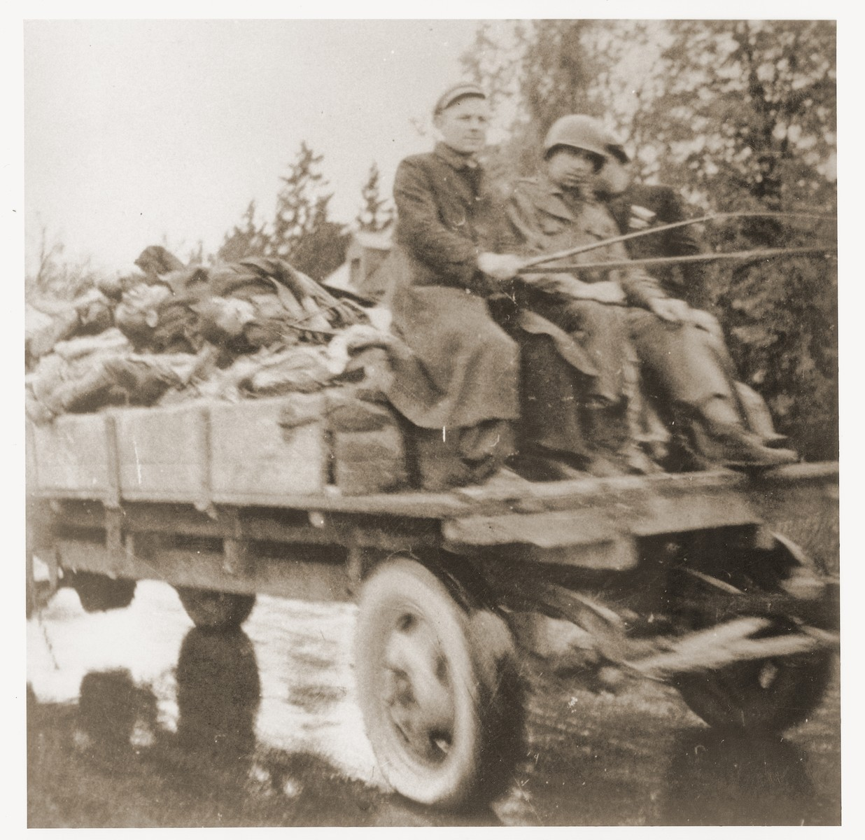 Wagons laden with corpses leave the Dachau concentration camp en route to a burial site.  Allied authorities required local farmers to drive their loaded carts through the town of Dachau as an education for the inhabitants.