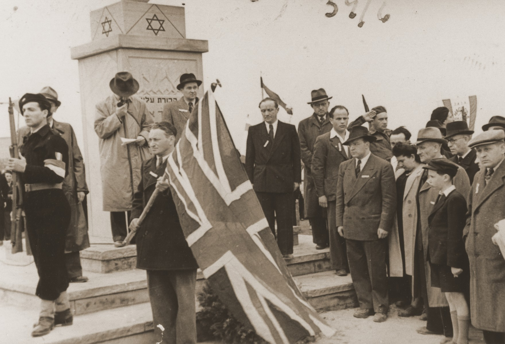 Jewish DPs take part in a public ceremony at the dedication of the Bergen-Belsen memorial.  Pictured in front of the pillar on the right are Paul Trepman and Raphael Olewski.  At the right are Josef Rosensaft, Shmayahu Bloch, Norbert Wollheim, Hadassah Bimko, Simcha Winik (saluting) and Shmuel Weintraub.