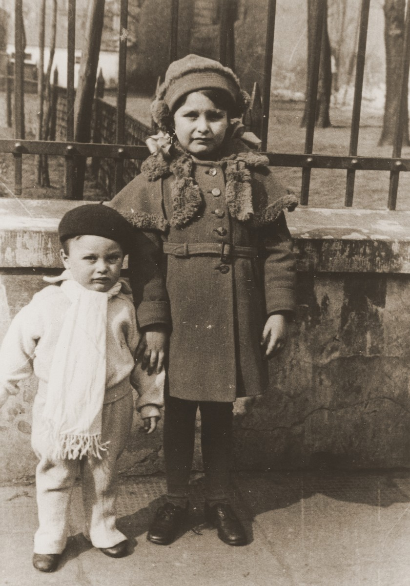 Portrait of two young Jewish children standing outside a park in Warsaw.  The children are the cousins of Rivka Radzinski.