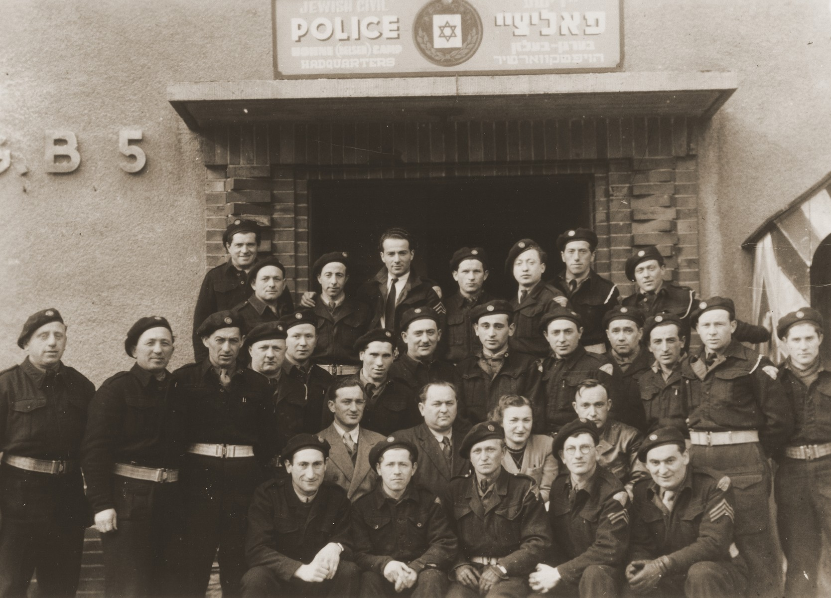 Group portrait of members of the Jewish police force in front of their headquarters at the Bergen-Belsen DP camp.  Those pictured include: second row: police chief Jaronowsky, secretary Hanka Altman.  Top row: third from left Moshe Stampfater, 4th from left Nandor Aron and 6th from left, Milehman.