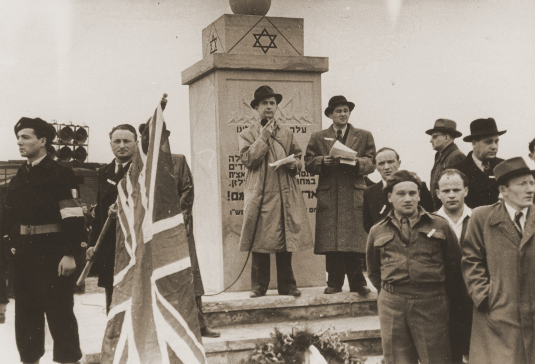 Jewish DPs take part in a public ceremony at the dedication of the Bergen-Belsen memorial.  In front of the memorial are Paul Trepman and Rafael Olewski.  Also pictured are Josef Rosensaft, Shmayahu Bloch, Winik, Karl Katz and Berel Dov Laufer.