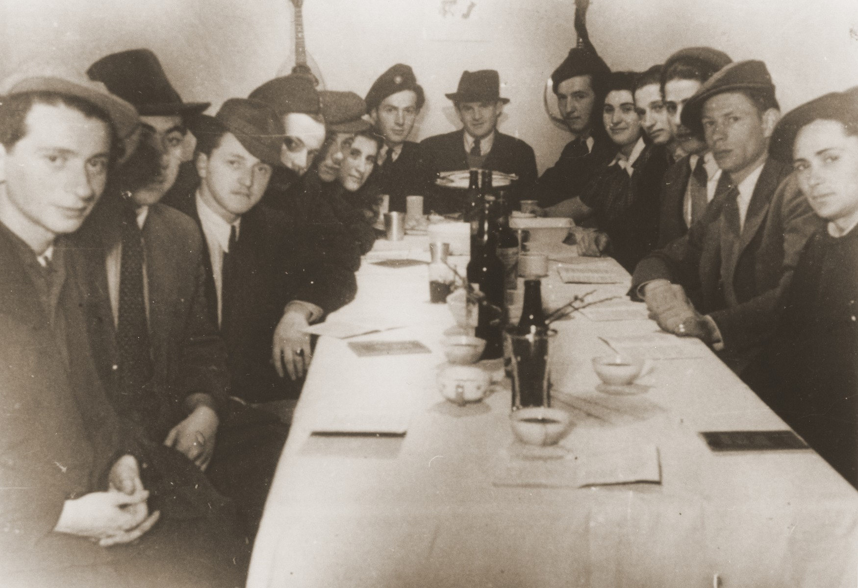 Members of the Kibbutz Haghibor hachshara hold a Passover seder in the Bergen-Belsen displaced persons camp.  Pictured in back at the head of the table is Laci (Leslie) Schwartz.